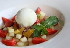 Eiscreme und Obstsalat auf weißer Tabelle Stockfotos