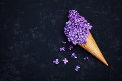 Eiscreme von lila Blumen im Waffelkegel auf schwarzem Hintergrund von oben, schönes Blumengesteck, Weinlesefarbe, flache Lage Lizenzfreies Stockfoto