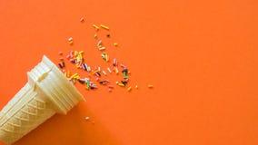 Eiscremebasis auf orange Hintergrund mit farbigem Regenbogen lizenzfreie stockbilder