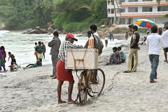 Eiscremeverkäufer auf einem beschäftigten Strand mit Fahrrad Stockbilder