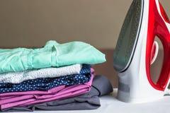Eisen auf dem Bügelbrett und der nicht-gebügelten Kleidung lizenzfreie stockfotos