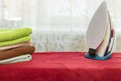 Eisen mit Tüchern auf Bügelbrett Stockfotografie