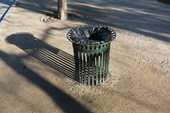 Eisenabfalleimer mit grünen Stangen im werfenden länglichen Schatten des Parks stockfoto