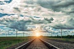 Eisenbahn bei Sonnenuntergang mit drastischem Himmel Sepia tonte Foto Stockbilder