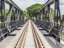Eisenbahn bildet Bahn auf Metallbrücke mit Bäumen und Himmel aus Stockfoto