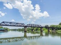 Eisenbahn bildet Bahn auf Metallbrücke mit dem Fluss und dem Himmel aus Stockbilder