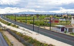 Eisenbahn, die durch eine kleine Stadt in Spanien überschreitet stockfoto