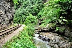 Eisenbahn in Guam-Schlucht auf einer Seite der Felsen, der anderen ein tiefer Abgrund und kochendem schnellem Fluss Lizenzfreie Stockbilder