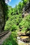 Eisenbahn in Guam-Schlucht auf einer Seite der Felsen, der anderen ein tiefer Abgrund und kochendem schnellem Fluss Stockbild