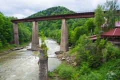 Eisenbahn und eine alte Hängebrücke über Gebirgsfluss Stockfoto
