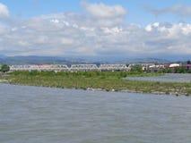 Eisenbahnbrücke über dem Fluss, die Berge auf dem Horizont, schöner bewölkter Himmel Lizenzfreies Stockfoto