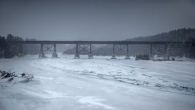 Eisenbahnbrücke über gefrorenem Fluss stockfoto
