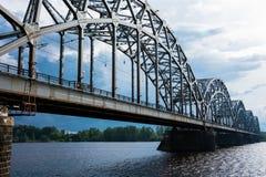 Eisenbahnbrücke Dzelzcela-Neigungen über Daugava-Fluss lizenzfreie stockbilder