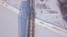 Eisenbahnbrücke für Zugverkehr über Winterfluß auf schneebedeckter Landschaftsbrummenansicht Suspendierungszugbrücke durch Winter stock footage