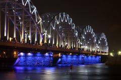 Eisenbahnbrücke nachts mit weiß-blauer Beleuchtung Stockfotografie