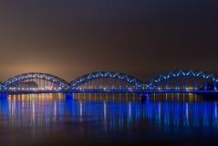 Eisenbahnbrücke Rigas mit Lichtern nachts Stockfoto