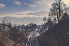 Eisenbahnlinie unter Baumlinie und Wintergebirgszug Stockbilder