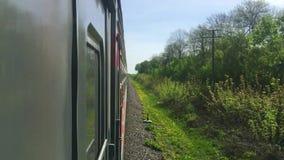 Eisenbahnreisekonzept Sich fortbewegender Zug mit den Passagierlastwagenwagen, die sich draußen durch Schiene in der schönen Ansi stock video footage
