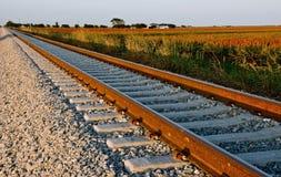 Eisenbahnspur nahe Ackerland am Sonnenuntergang. Stockfotos