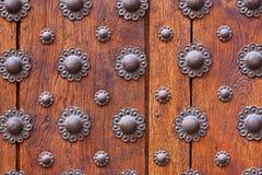 Eisenblumenmuster über hölzerner Tür Stockfotografie