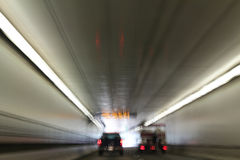 Eisenhower Tunnel in Colorado Blurred. Inside of eisenhower tunnel in Colorado with motion blur and vehicle brake lights and exit ahead royalty free stock photography