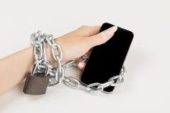 Eisenkette mit dem Verschluss schließt die weibliche Hand und den Smartphone zusammen an das Konzept der Abhängigkeit am Handy lizenzfreies stockfoto