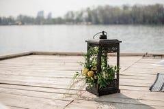 Eisenlaterne verziert mit tropischen Blumen als Hochzeitsdekor auf der Flussbank Lizenzfreies Stockbild
