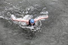 Eisenmann - Schwimmer, der den Schmetterlingsanschlag im dunklen Ozeanwasser durchführt Lizenzfreie Stockfotos
