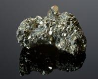 Eisenpyrite auf einer schwarzen reflektierenden Oberfläche Lizenzfreies Stockfoto