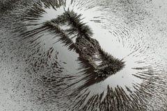 Eisenstaub, der das Magnetfeld nahe einer Magnetstange auf weißem Hintergrund zeigt lizenzfreie stockfotos