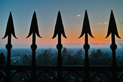 Eisenzaun kippt Retro- gegen Sonnenuntergang um Stockbild
