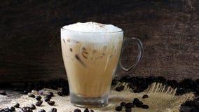 Eisespressokaffee mit Milch setzte an eine hölzerne Tabelle mit dunklen Röstkaffeebohnen Lizenzfreie Stockfotografie