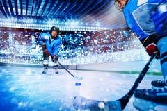 Eishockeyspieler, der dem Mannschaftskameraden den Kobold führt lizenzfreie stockfotografie