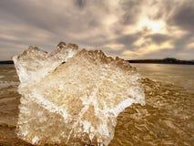 Eisige Blätter, die auf sandigem Strand schmelzen Ende von lang und crue Winterkommen Detail der Eisscholle Lizenzfreie Stockbilder