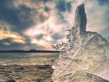 Eisige Blätter, die auf sandigem Strand schmelzen Ende von lang und crue Winterkommen Detail der Eisscholle Stockbild