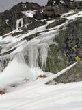Eisige Gebirgsfelsen Felsen bedeckt mit grüner Beschichtung Eiszapfen, die von den Felsen hängen lizenzfreie stockfotos