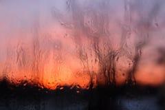 Eisige Muster auf Glas, Sonnenuntergang ist in einem Fenster Lizenzfreie Stockfotos