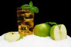 Eisiger Apfelsaft, Eiswürfel und Apfel mit Blättern auf Schwarzem auf Schnee Stockbild