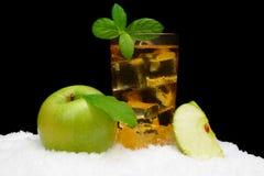 Eisiger Apfelsaft, Eiswürfel und Apfel mit Blättern auf Schwarzem auf Schnee Stockbilder