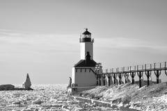 Eisiger Leuchtturm im Winter mit Mann auf Schritten Lizenzfreie Stockfotos