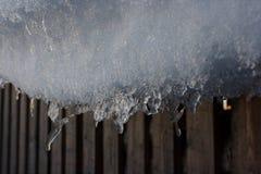 Eisiger Schneerand, der vom Dach hängt stockfotos
