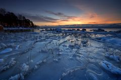 Eisiger Strand im Sonnenaufgang. stockfoto
