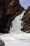 Eisiger Wasserfall an der Felsenklippe in der Winterzeit Lizenzfreie Stockfotos