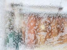 Eisiges Muster auf Glaswinterfenster, Blick durch Glas Stockfotografie