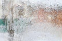Eisiges Muster auf Glaswinterfenster, Blick durch Glas Stockfoto