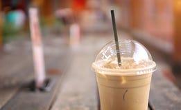 Eiskaffee Latte in der Mitnehmerschale auf hölzerner Tabelle Mitnehmereis Lat stockfoto