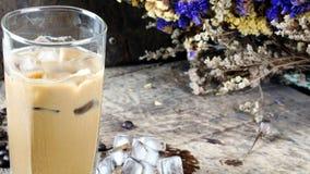 Eiskaffee setzte an eine hölzerne Tabelle mit dunklen Röstkaffeebohnen Lizenzfreie Stockfotos