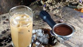 Eiskaffee setzte an eine hölzerne Tabelle mit dunklen Röstkaffeebohnen Stockfotos