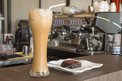 Eiskaffee und Schokoladenkuchen auf hölzerner Tabelle im Café lizenzfreie stockfotografie