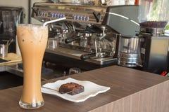 Eiskaffee und Schokoladenkuchen auf hölzerner Tabelle im Café lizenzfreies stockbild